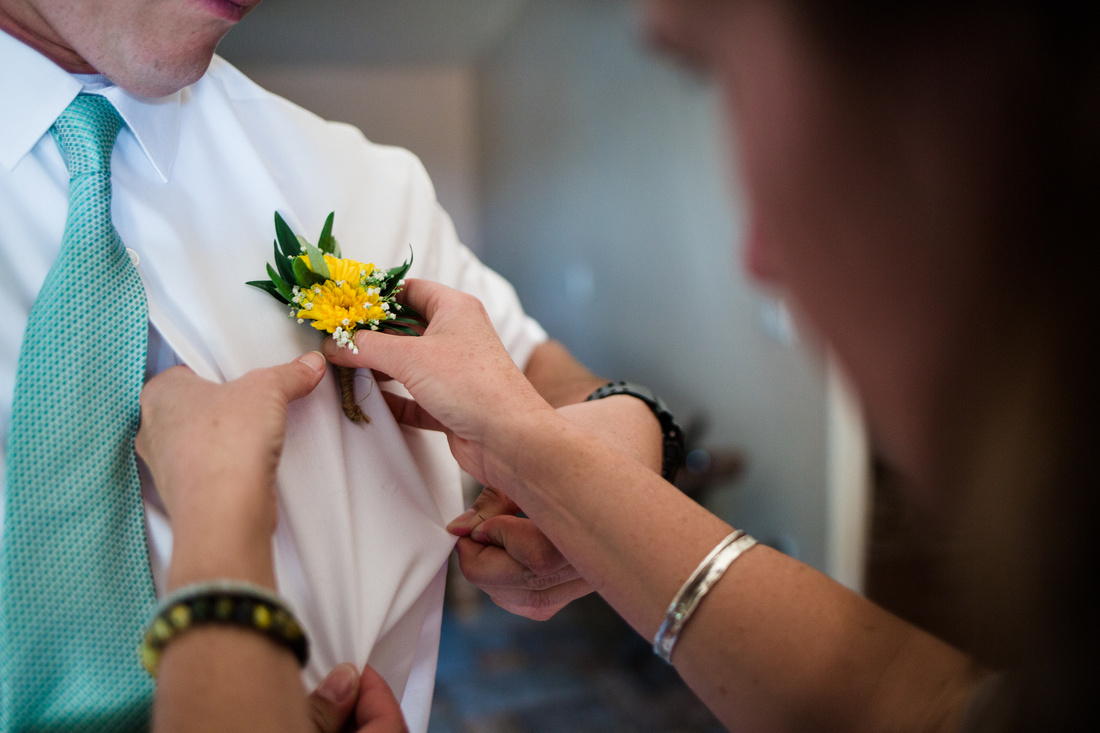 Woman pinning a boutonnière on the groom in preparation for his wedding in Ojai, California, shot by Alison Photography.