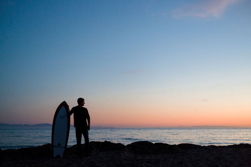 Silhouette portrait of a man with a surf board at Goleta Beach in Santa Barbara.
