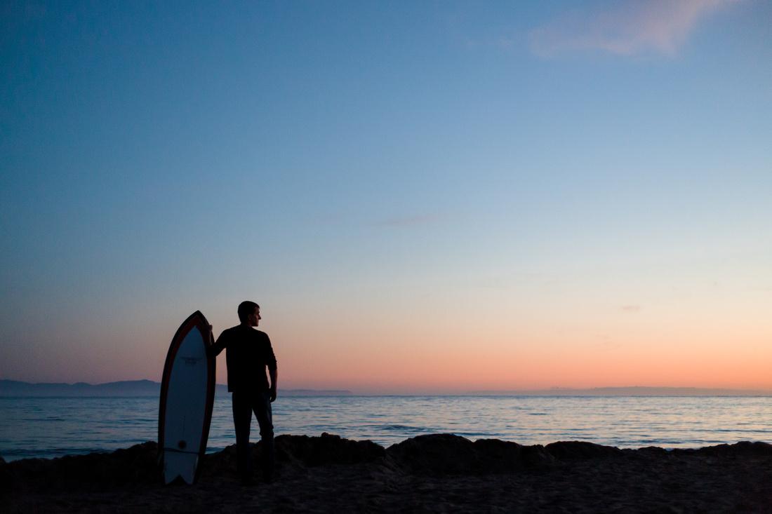 Silhouette portrait of a man with a surf board at Goleta Beach in Santa Barbara.