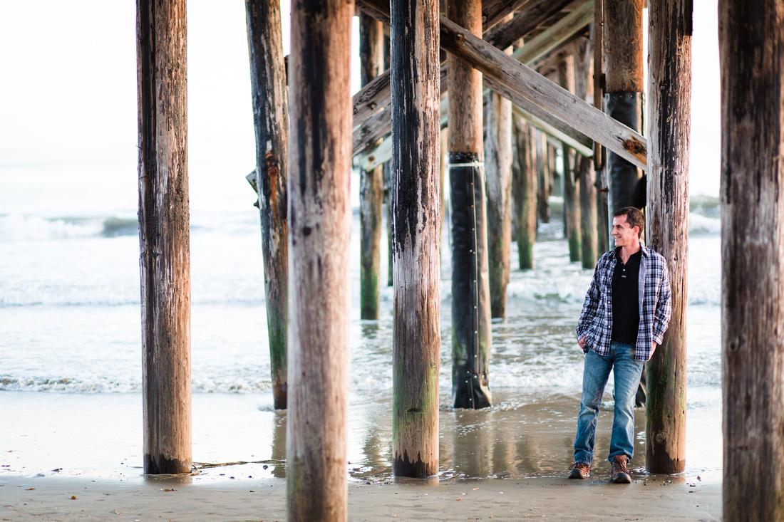 Portrait of a man under Goleta Pier in Santa Barbara with the ocean in the background.