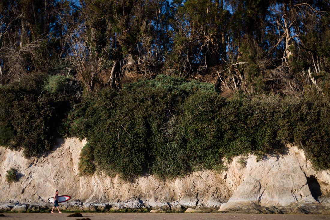 Portrait of a man with a surfboard at Goleta Beach in Santa Barbara.