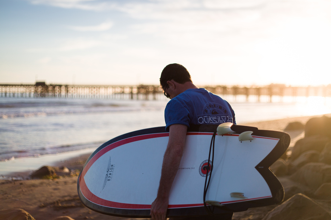 Portrait of a man with a surfboard at Goleta Beach in Santa Barbara at sunset with the pier in the background.