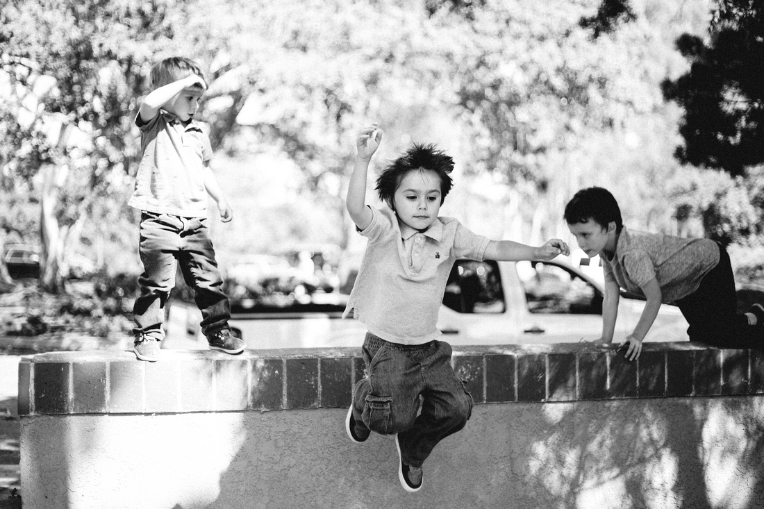 Boys playing on and jumping off of a wall.