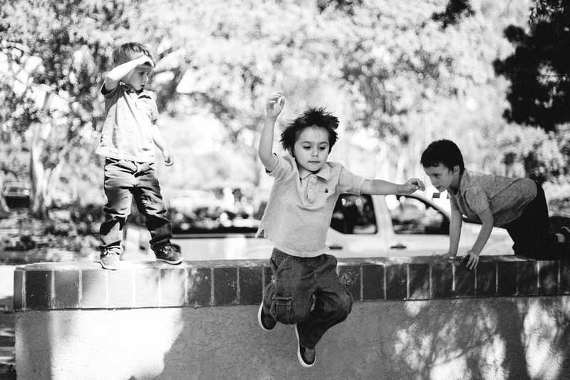 Black and white photo of three young boys playing on, and jumping off, a wall.