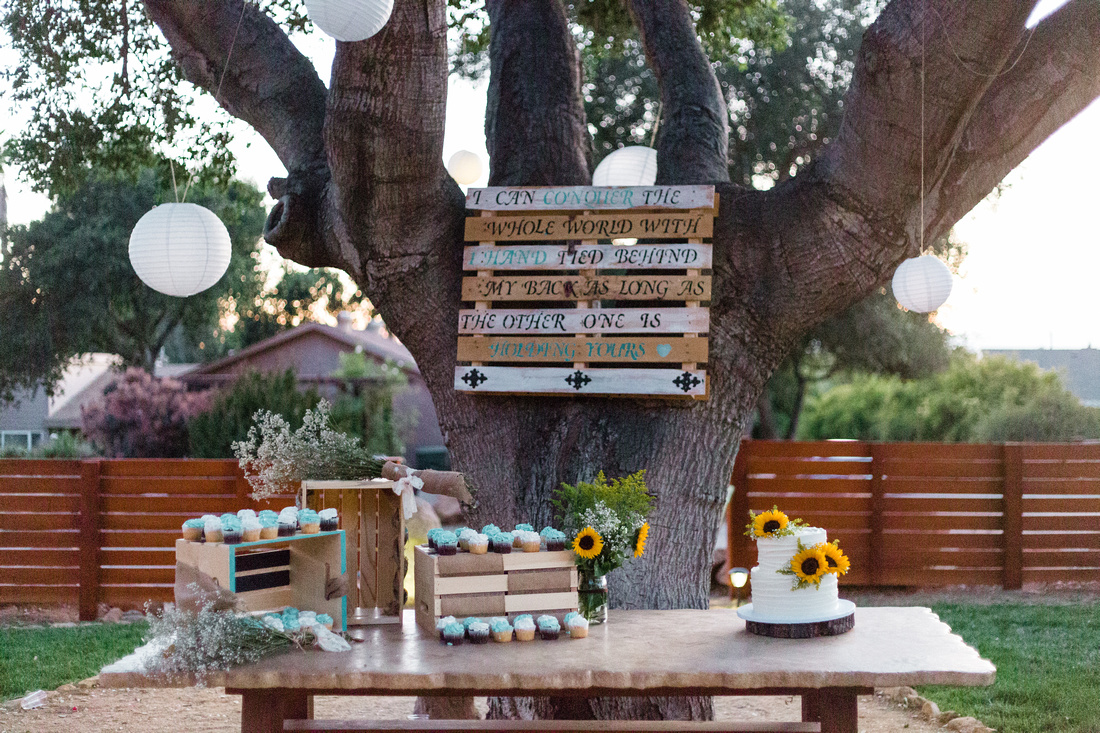 Wedding cake with sunflower decoration and cupcakes at rustic chic Summer wedding reception in Ojai, California, shot by Alison Photography.