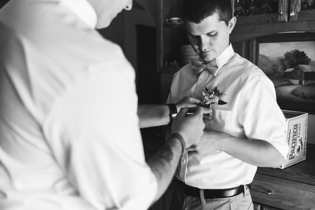 Groom pinning a boutonnière on his brother in preparation for his wedding in Ojai, California, shot by Alison Photography.