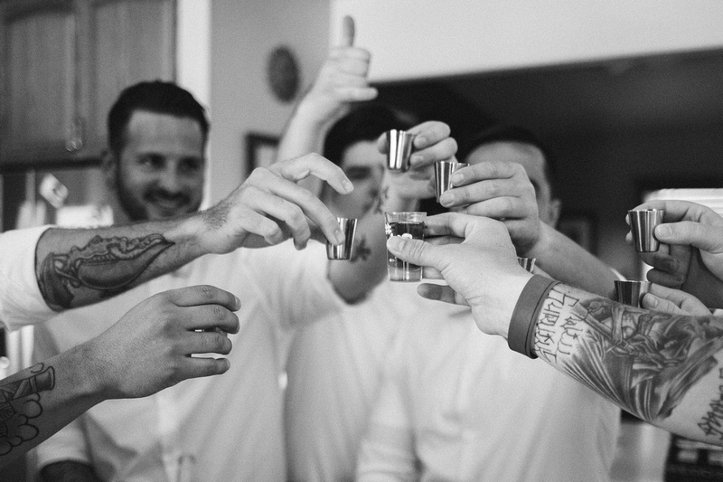 Tattooed groomsmen taking shots before a rustic chic wedding in Ojai, California, shot by Alison Photography.