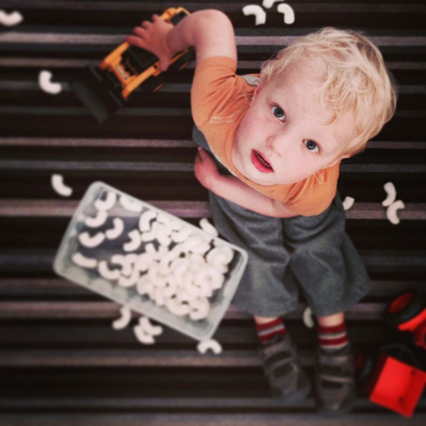 Cute toddler playing with a truck and packing peanuts on a striped carpet.
