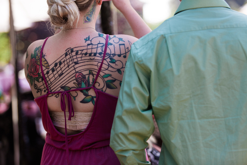 Girl with a music-themed tattoo at a rustic chic wedding ceremony in Ojai, California, shot by Alison Photography.