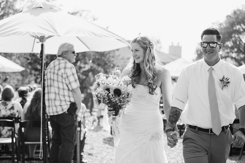 Black and white shot of bride and groom leading the recessional at rustic chic wedding ceremony in Ojai, California, shot by Alison Photography.